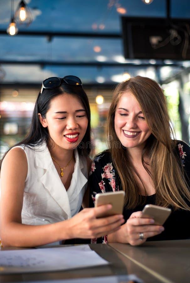 Żeńscy przyjaciele używa telefon w restauraci zdjęcie stock