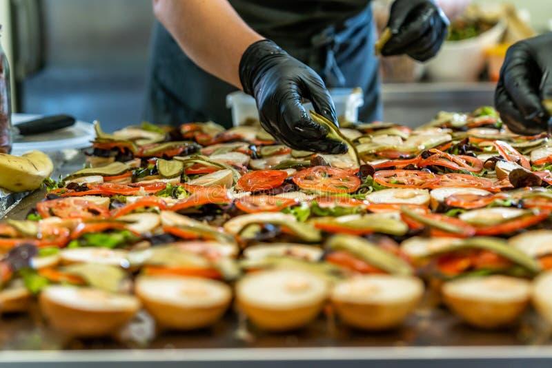 Żeńscy szefa kuchni kładzenia składniki hamburgery na Pokrojonym chleba rozszerzaniu się na stole w Czarnych rękawiczkach - pojęc fotografia stock