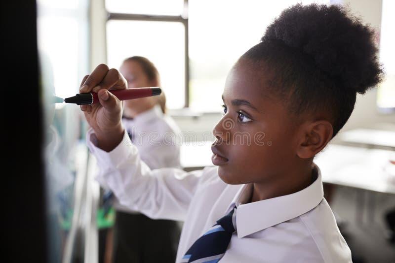 Żeńscy szkoła średnia ucznie Jest ubranym mundur Używać Interaktywnego Whiteboard Podczas lekcji obrazy stock