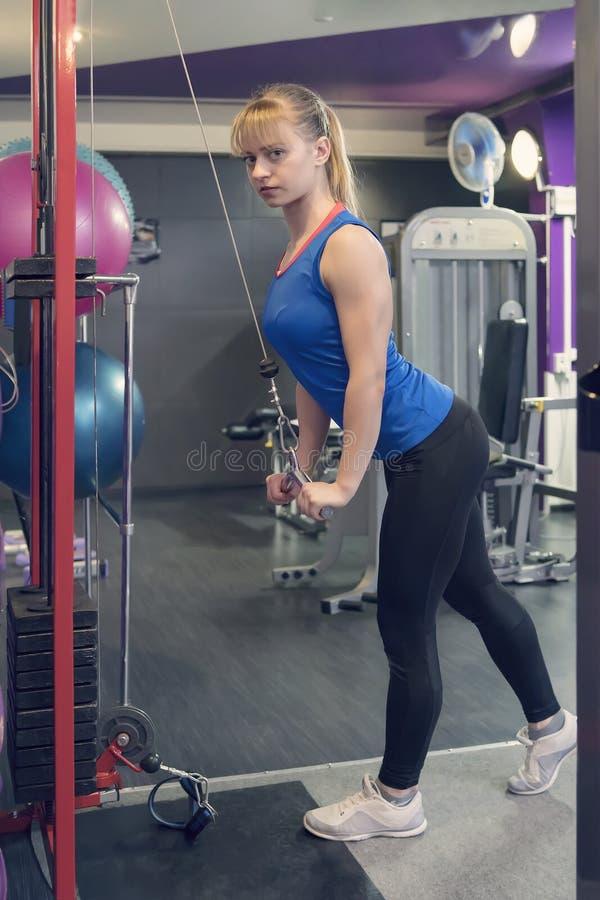 Żeńska atleta na wioślarskiej maszynie na przecinającej rywalizaci podnosi baru dźwignięcie ciężary Atleta w błękitnym kostiumu p fotografia stock