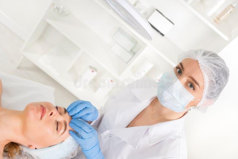 Żeńska beautician lekarka z pacjentem w wellness centrum E zdjęcia royalty free