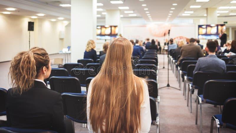 Żeńska głośnikowa daje prezentacja w odczytowej sala przy uniwersyteckim warsztatem Tylni widok nierozpoznani uczestnicy słucha l fotografia stock