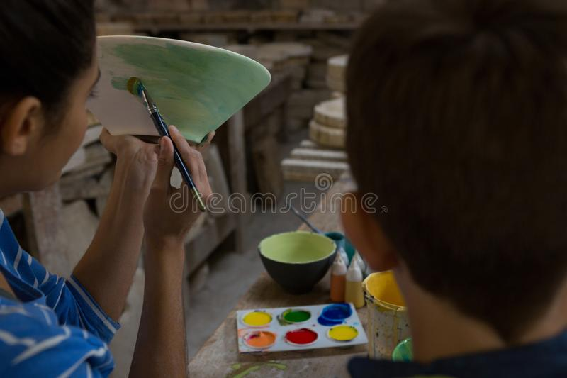 Żeńska garncarka pomaga jej syna w malować puchar obrazy royalty free
