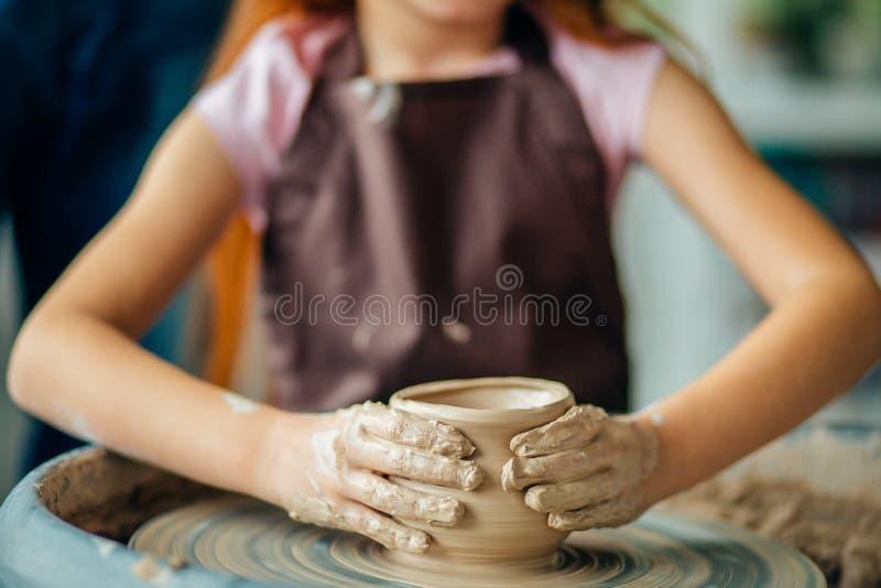 Żeńska garncarka pracuje przy miotania kołem przy studiiem Gliniany warsztat fotografia royalty free