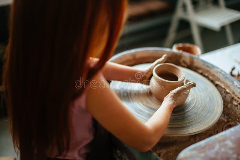 Żeńska garncarka pracuje przy miotania kołem przy studiiem Gliniany warsztat zdjęcia royalty free