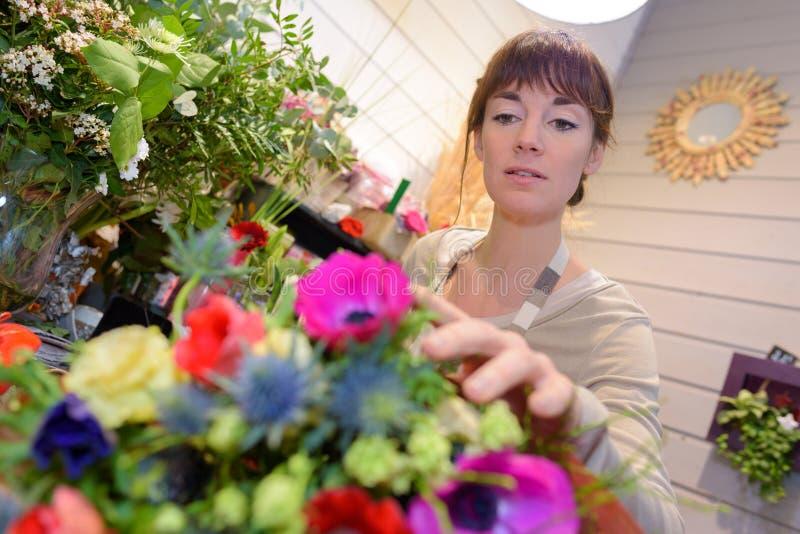 Żeńska kwiaciarnia bierze kwiatu fotografia royalty free