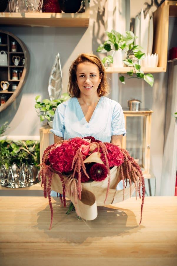 Żeńska kwiaciarnia dekoruje kwiaty w sklepie fotografia stock
