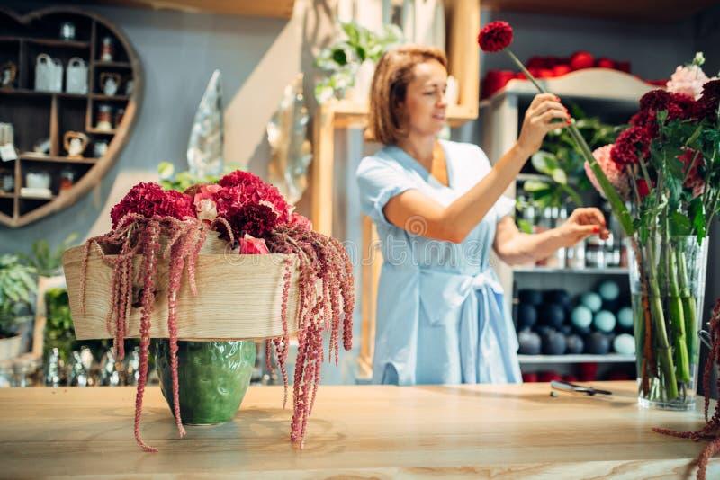 Żeńska kwiaciarnia dekoruje kwiaty w sklepie zdjęcie stock