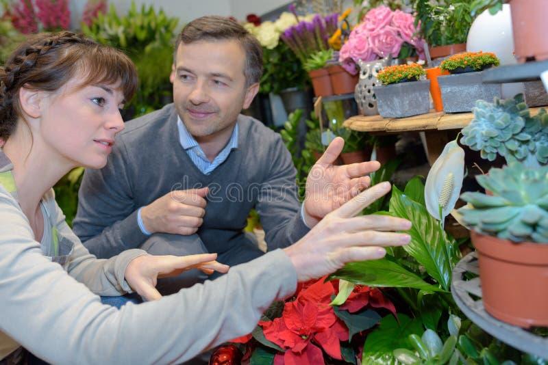 Żeńska kwiaciarnia i klient w kwiatu sklepie obrazy royalty free