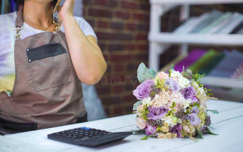 Żeńska kwiaciarnia opowiada na telefonie dyskutuje koszt bukiet z klientem w kwiatu sklepie zdjęcia royalty free
