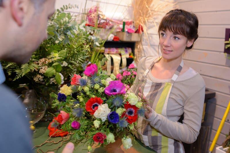 Żeńska kwiaciarnia pracuje w kwiat sekci przy sklepem zdjęcie royalty free