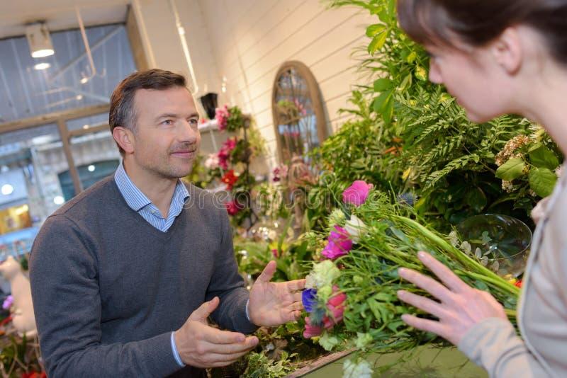 Żeńska kwiaciarnia radzi męskiego klienta fotografia royalty free