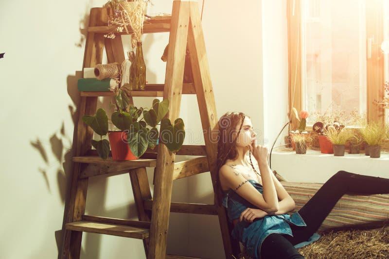 Żeńska moda, piękno i reklamy pojęcie, wzorcowy hipisa lub dziewczyny obsiadanie na sianie przy drewnianą drabiną fotografia stock