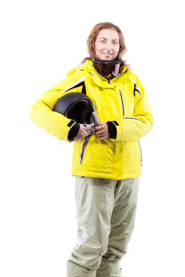 Żeńska narciarka z hełmem w żółtej kurtce zdjęcie stock
