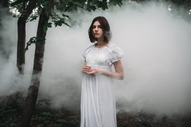 Żeńska ofiara w biel sukni w mglistym lesie obrazy stock