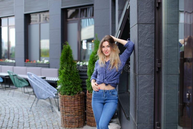 Żeńska osoba jest ubranym błękitnych cajgi i koszula, stojący blisko budynku i zielonej rośliny obraz royalty free