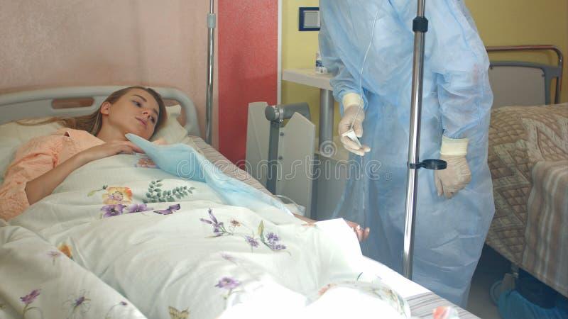 Żeńska pielęgniarka sprawdza wkraplacz z lekarstwem, odpłaca się pierwszą pomoc pacjent zdjęcie royalty free
