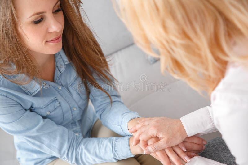 Żeńska psychologyst terapii sesja z klientem indoors siedzi mienia wręcza zakończenie zdjęcie royalty free