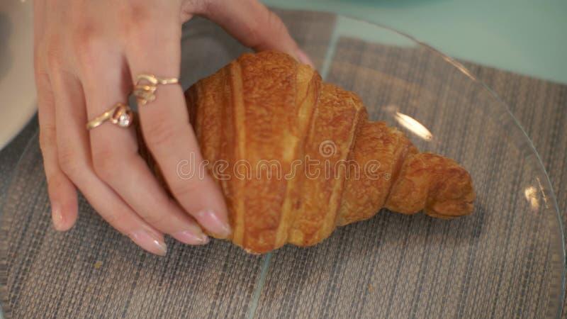 Żeńska ręka bierze croissant od szklanego talerza przy stołem w kawiarni zakończeniu up zdjęcie royalty free