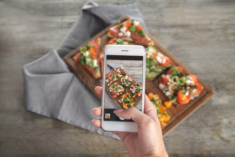 Żeńska ręka bierze fotografię jedzenie obraz royalty free