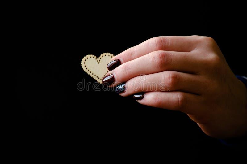 Żeńska ręka daje drewnianemu sercu na czarnym tle zdjęcie royalty free