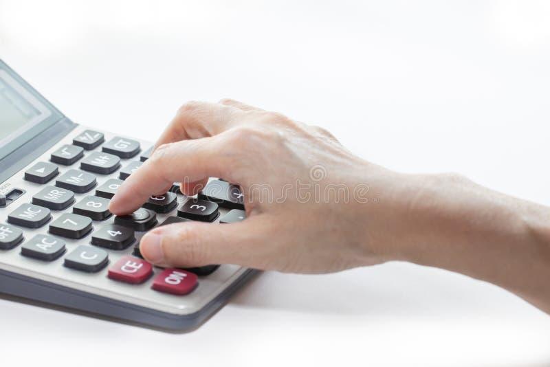 Żeńska ręka dotyka guziki na kalkulatorze, w górę i odizolowywa na białym tle obrazy stock