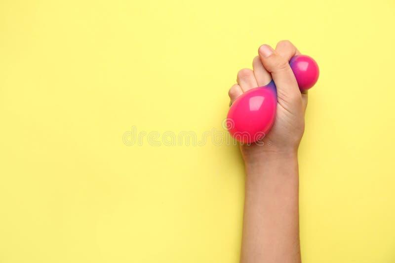 Żeńska ręka gniesie stres piłkę na koloru tle zdjęcia stock
