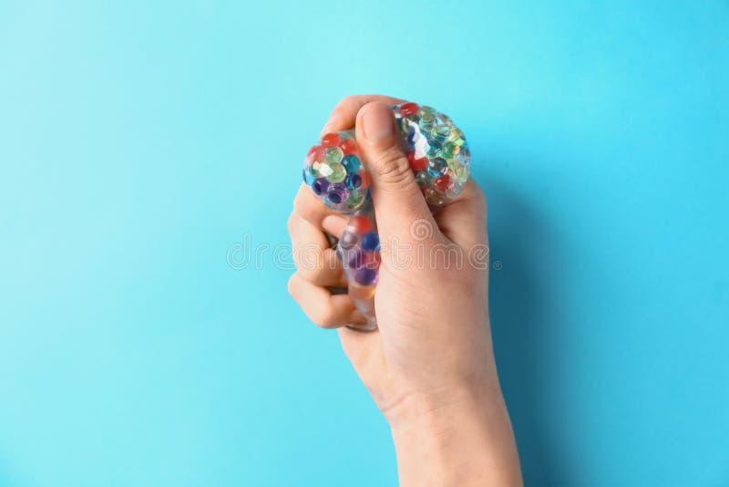 Żeńska ręka gniesie stres piłkę na koloru tle obraz stock
