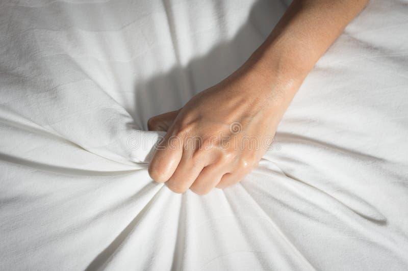 Żeńska ręka ma płeć na łóżku obraz stock