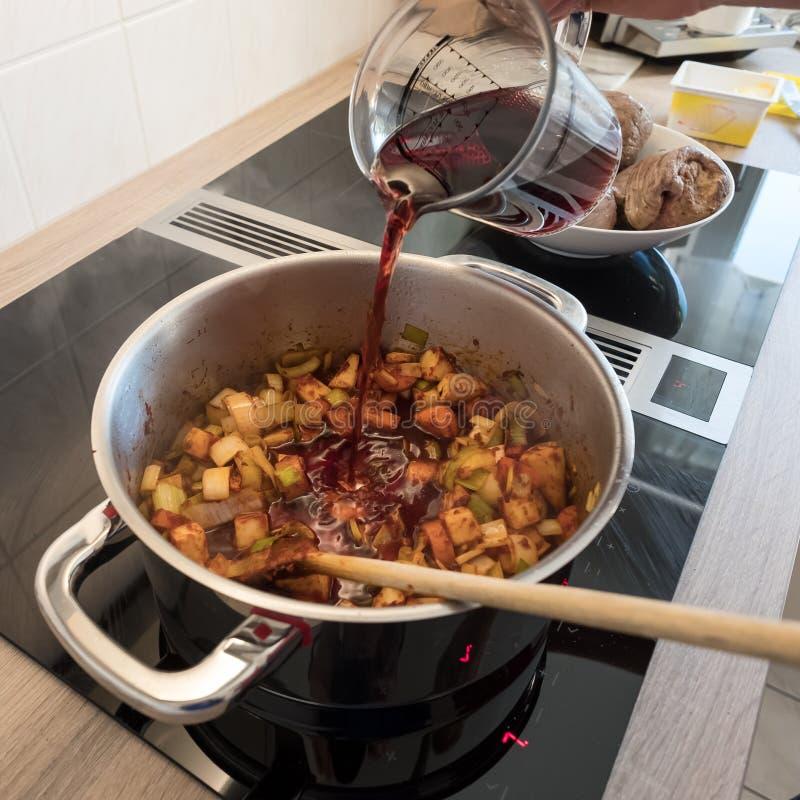 Żeńska ręka nalewa czerwone wino w prażaka warzywo obrazy royalty free