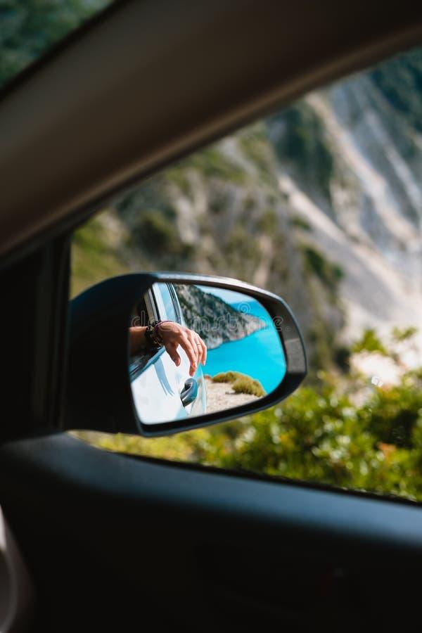 Żeńska ręka odzwierciedlająca w samochodowym bocznego widoku lustrze Błękitne morza śródziemnomorskiego i bielu skały w tle fotografia stock