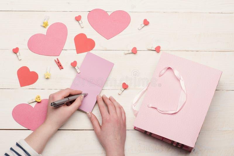 Żeńska ręka pisze miłości wiadomości na różowym nutowym papierze fotografia stock