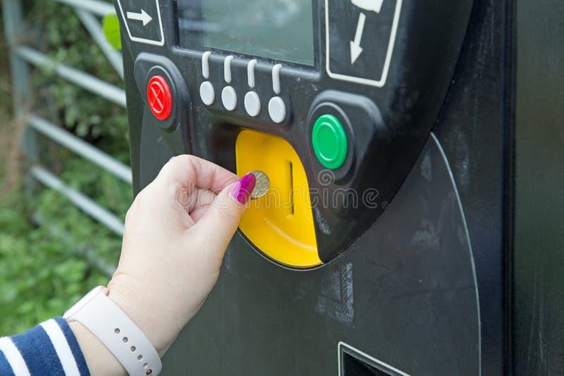 Żeńska ręka stawia monetę w parking metr obrazy royalty free