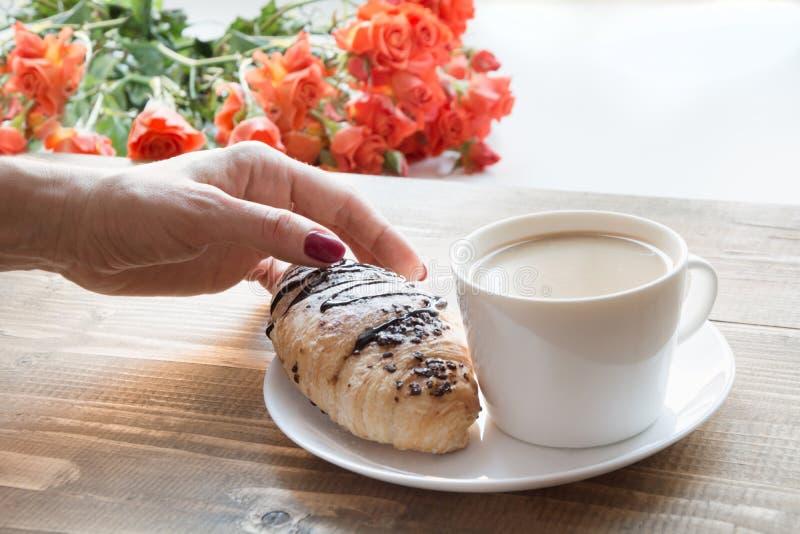 Żeńska ręka trzyma świeżo piec czekoladową filiżankę kawy i croissants śniadaniowy kawowy pojęcia filiżanki jajko smażący fotografia stock