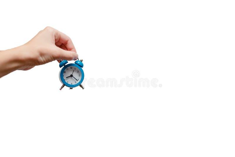Żeńska ręka trzyma budzika błękitny małego zdjęcie royalty free