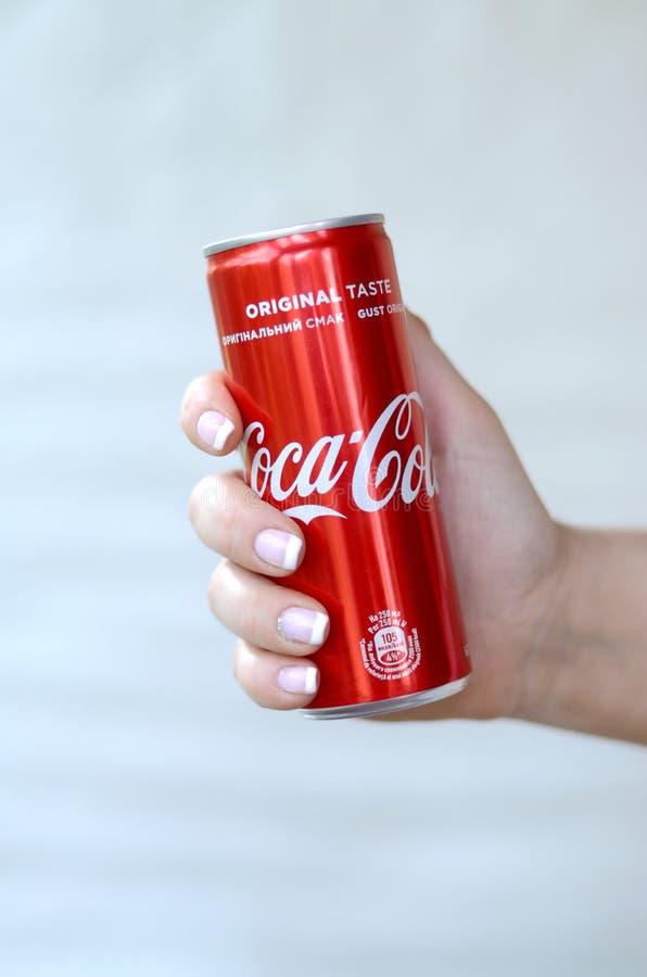 Żeńska ręka trzyma czerwonego koka-kola blaszaną puszkę na biel ściany tle zdjęcia stock