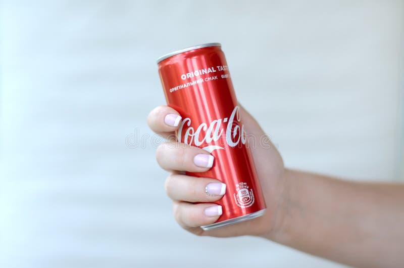 Żeńska ręka trzyma czerwonego koka-kola blaszaną puszkę na biel ściany tle obraz stock