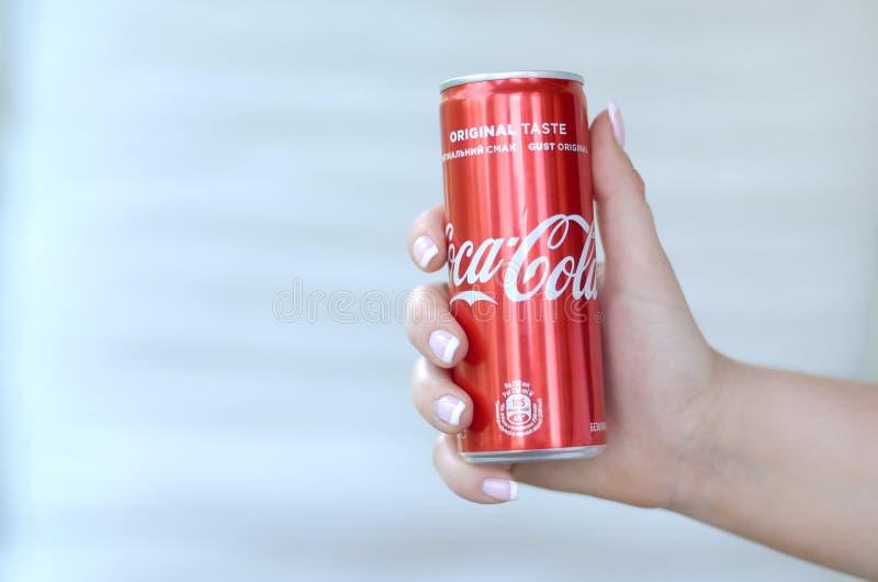 Żeńska ręka trzyma czerwonego koka-kola blaszaną puszkę na biel ściany tle zdjęcia royalty free