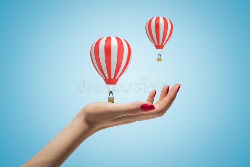 Żeńska ręka trzyma dwa gorące powietrze balonu na błękitnym tle obraz royalty free