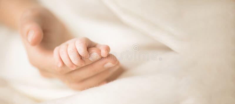 Żeńska ręka trzyma jej nowonarodzoną dziecka ` s rękę Mama z jej dzieckiem Macierzyński, rodzinny, narodziny pojęcie Odbitkowa pr zdjęcia royalty free