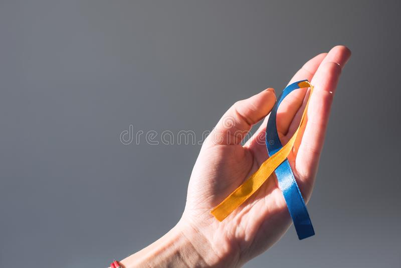 Żeńska ręka trzyma puszka syndromu dnia symbol błękitny i żółty faborek obraz royalty free