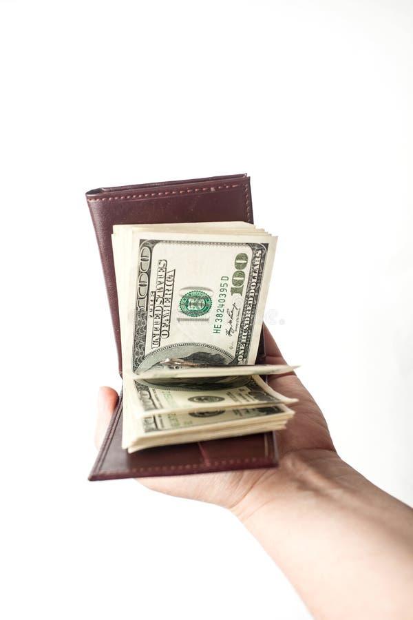 Żeńska ręka trzyma rozpieczętowanego brązu portfel z gęstym zwitkiem rachunki Odizolowywający nad białym tłem pionowo zdjęcia stock