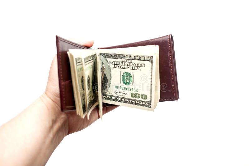 Żeńska ręka trzyma rozpieczętowanego brązu portfel z gęstym zwitkiem rachunki Odizolowywający nad białym tłem zdjęcie stock