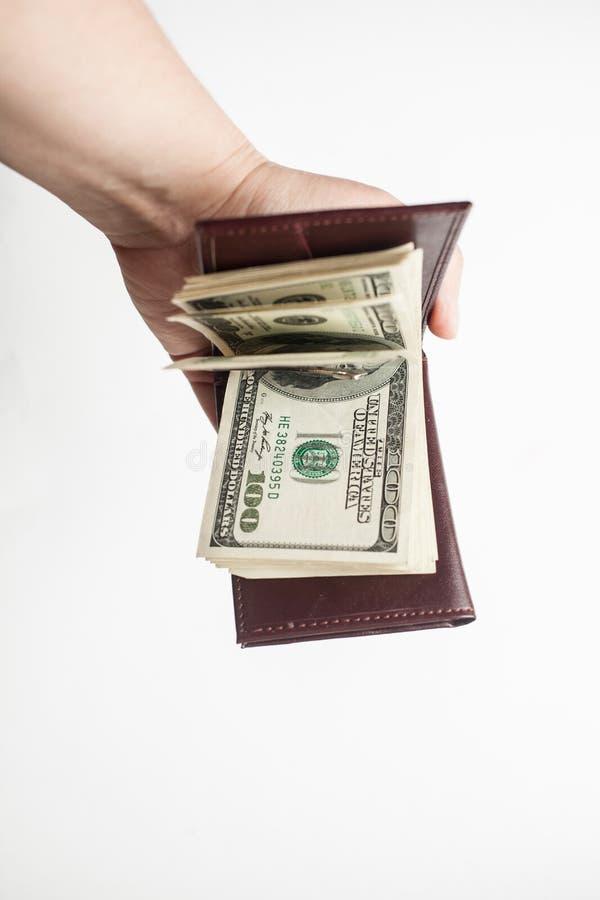Żeńska ręka trzyma rozpieczętowanego brązu portfel z gęstym zwitkiem sto dolarowych rachunków Odizolowywający nad białym tłem zdjęcia royalty free