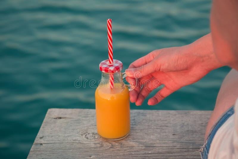 Żeńska ręka trzyma szklaną butelkę sok pomarańczowy na drewnianym doku obraz stock