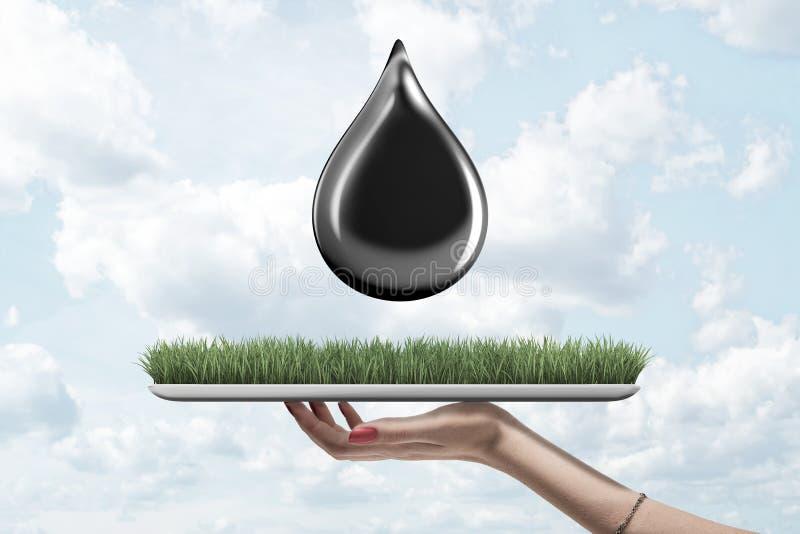 Żeńska ręka trzyma zielonej trawy deskę z czerń oleju kroplą na niebieskiego nieba tle ilustracja wektor