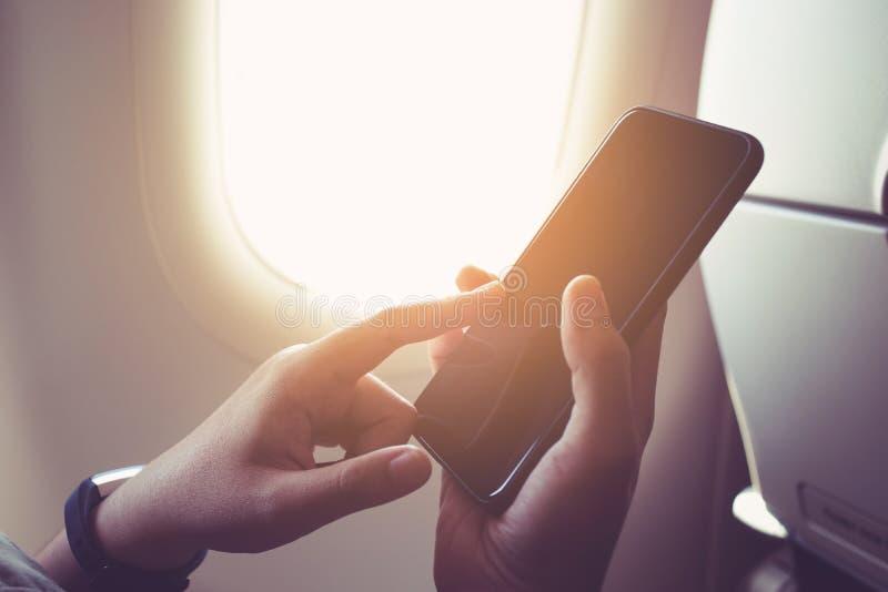 Żeńska ręka używać smartphone na samolocie z okno zdjęcia stock