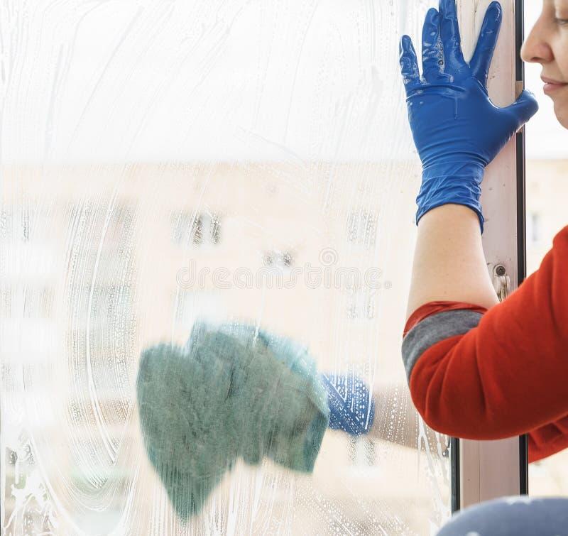 Żeńska ręka w błękitnych rękawiczkach czyści okno zdjęcie royalty free