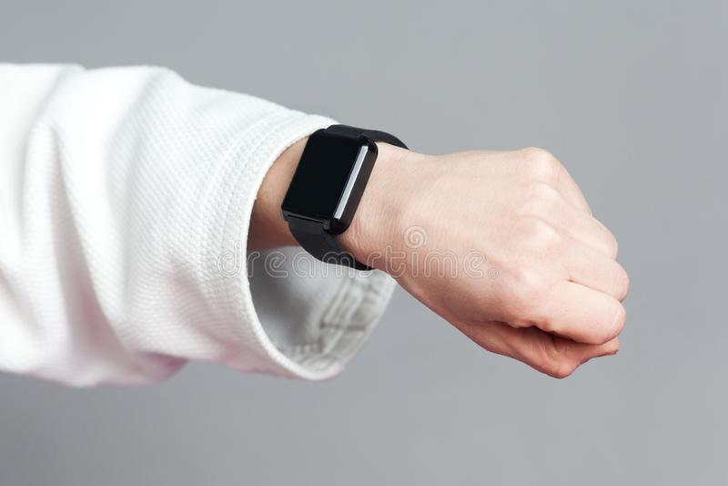 Żeńska ręka w białym rękawie z smartwatch pokazuje kierowe akademie królewskie fotografia royalty free