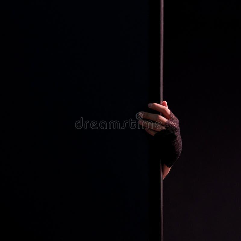Żeńska ręka w czarnej rękawiczka chwytów krawędzi ściana Czarny tło Kwadratowa rama Zakończenie Tematu wakacje Halloween mistyczn obrazy stock